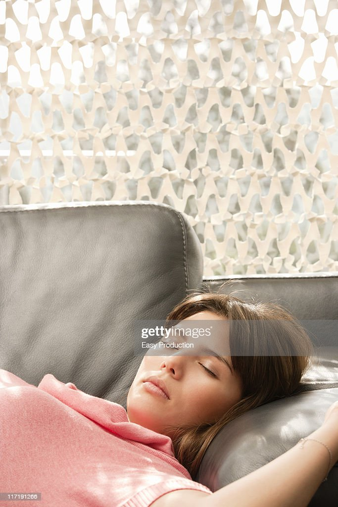 Young woman relaxing on a sofa : Stock Photo