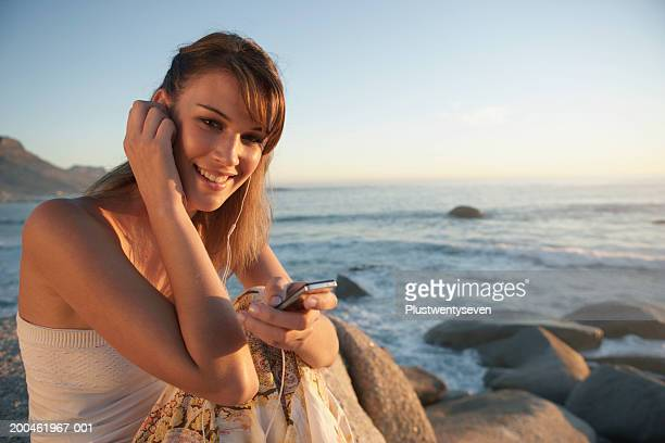 Young woman relaxing on beach at dusk, holding mobile phone, portrait