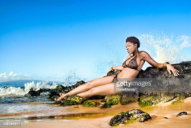 Young Woman Relaxing on Beach Near Rocks