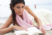 Young woman relaxing on beach, reading book, close-up, potrait