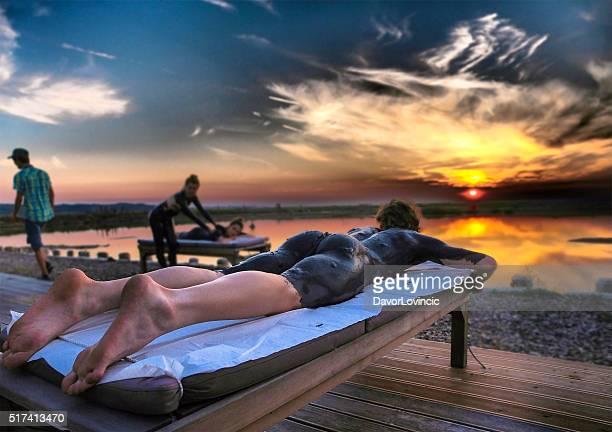 Junge Frau entspannend auf Bett mit Sonnenuntergang über dem Wasser