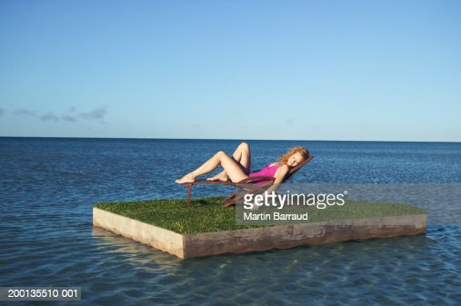 Young woman relaxing on grass topped raft at sea