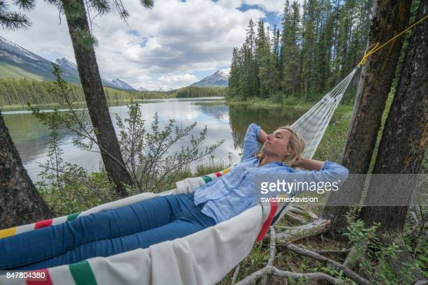 Young woman relaxing on hammock by the lake