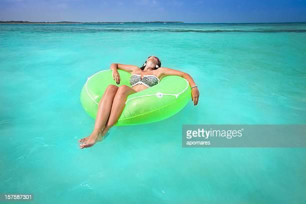 Jeune femme de détente dans un tube pneumatique plage turquoise