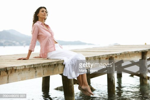Young woman relaxing on jetty : Stock Photo