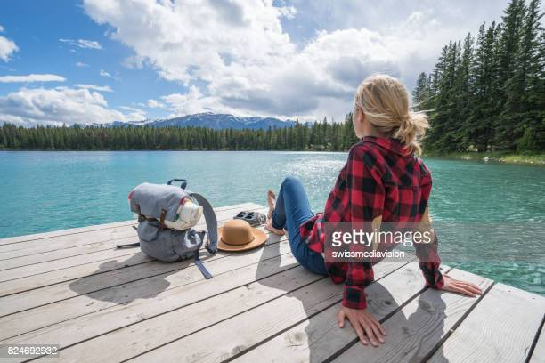 Young woman relaxing on lake pier