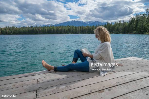 Young woman relaxing on lake pier with book