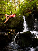 Young woman relaxing on rock near waterfall