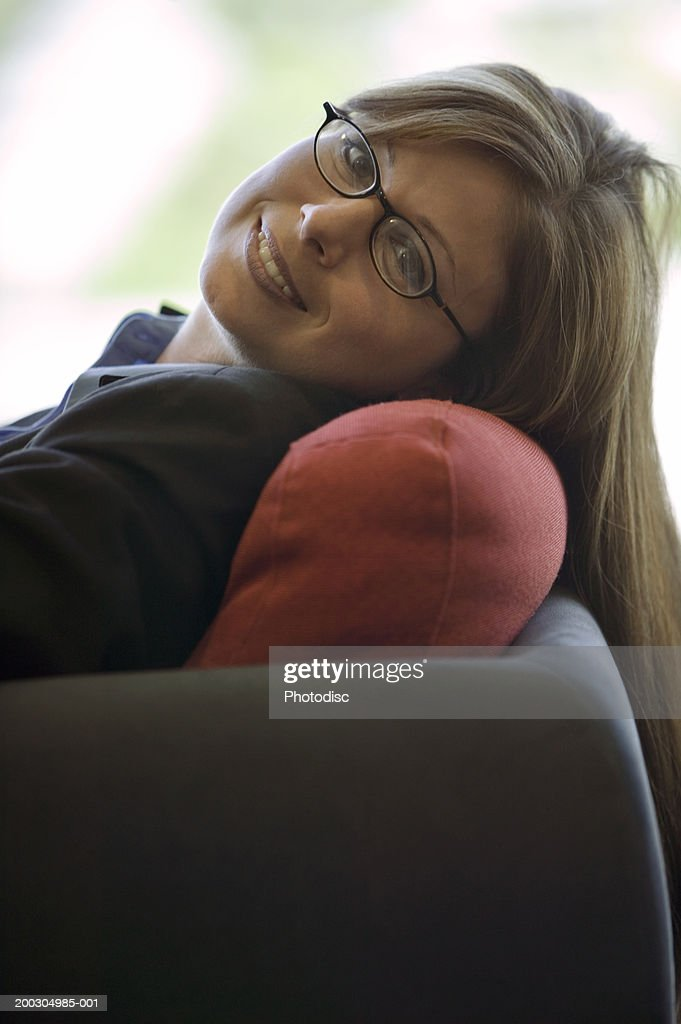 Young woman relaxing on sofa, portrait : Stock Photo