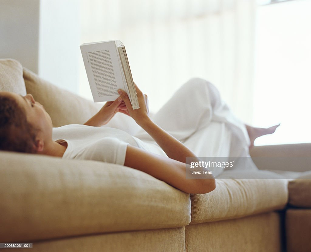 Young woman relaxing on sofa reading book, low angle view : Stock Photo