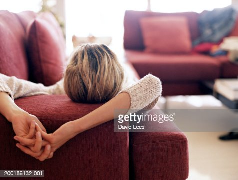 Young woman relaxing on sofa, rear view, close-up : Stock Photo
