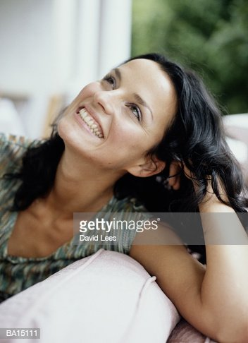 Young woman relaxing on sofa, smiling, close-up : Stock Photo