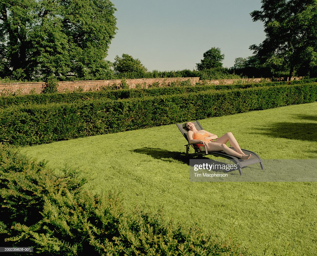 Young woman relaxing on sun lounger in garden, laughing : Stock Photo