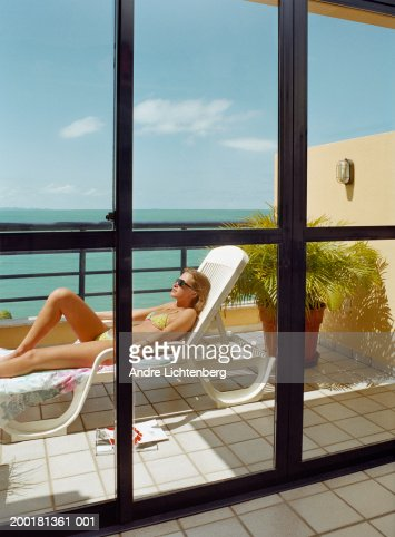 Young woman relaxing on sun lounger on balcony view for Balcony sunbathing