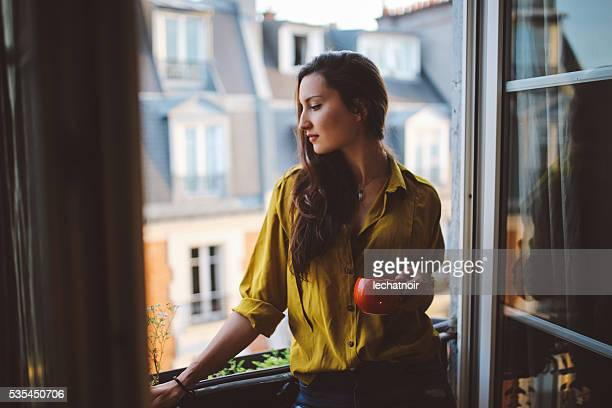 Young woman relaxing on the balcony of her Parisian apartment