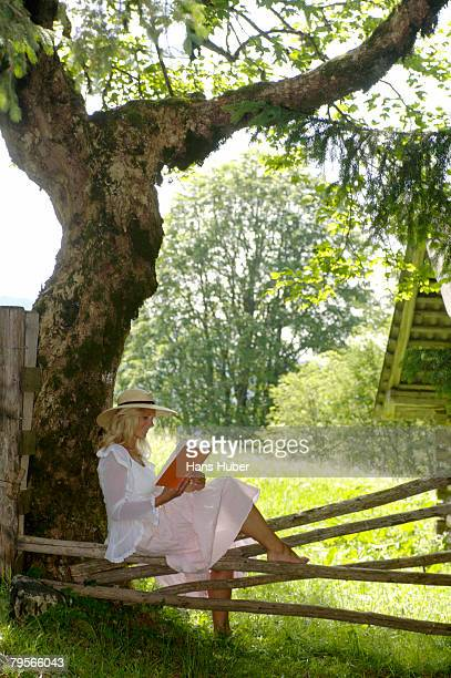 'Young woman relaxing under tree, reading book'