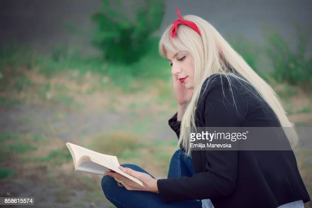 Young woman relaxing while reading a book at the park