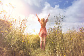 young woman relaxing with arms raised to the sky in the middle of a meadow