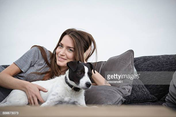 Young woman relaxing with dog on couch