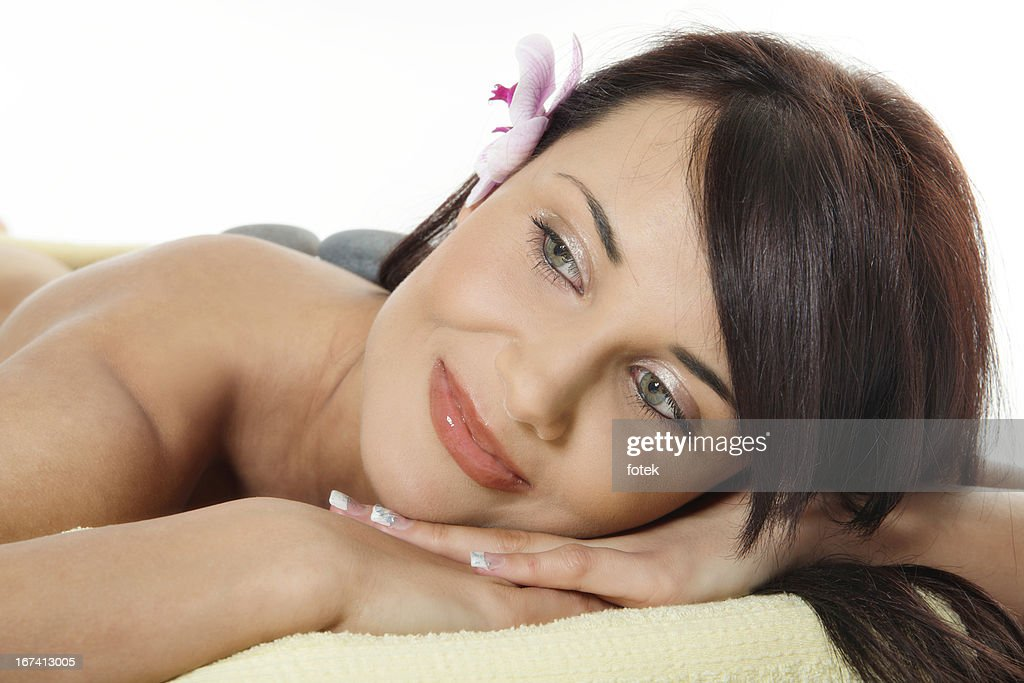 Young woman relaxing with flower and hot stones : Stockfoto