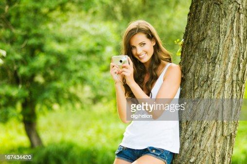 Mujer joven relajante con cámara de fotos : Foto de stock