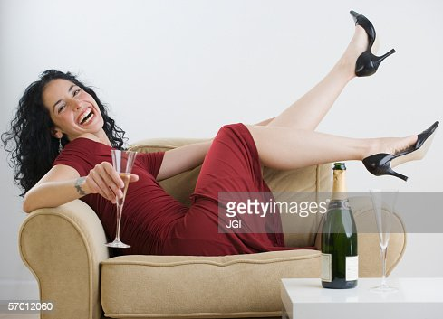 Young woman relaxing with wine at dinner party