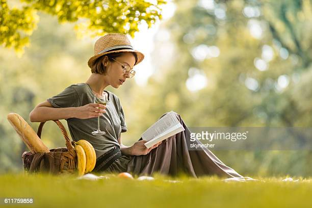Young woman relaxing with wineglass and reading book at picnic.