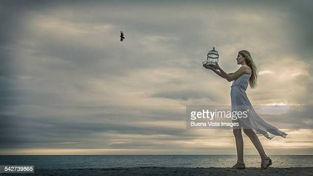 Young woman releasing a bird from a cage