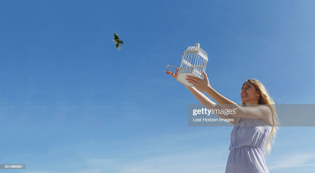 Young woman releasing bird from cage toward blue sky