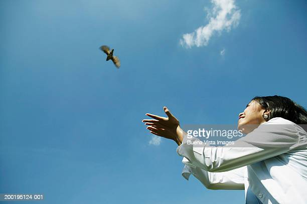 Young woman releasing bird smiling, low angle view