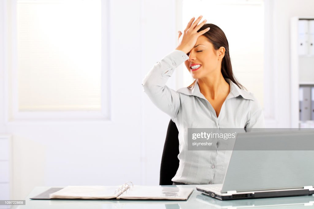 Young woman remembered something sitting in the office. : Stock Photo