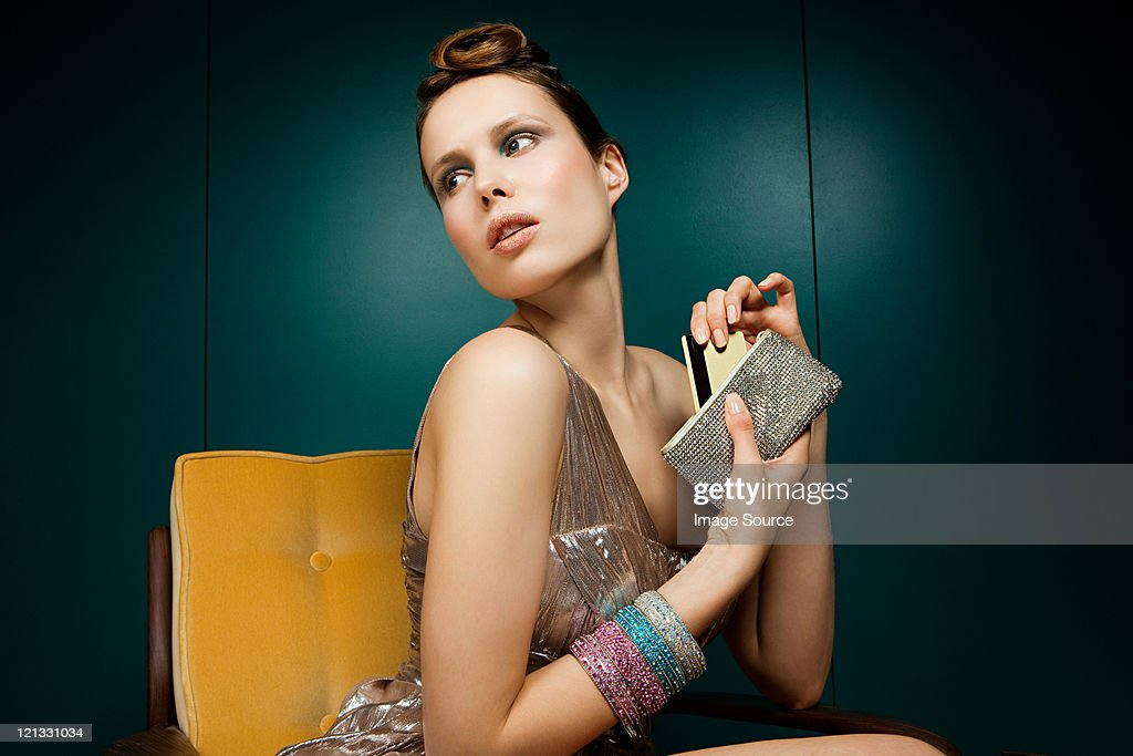 Young woman removing credit card from purse : Stock Photo