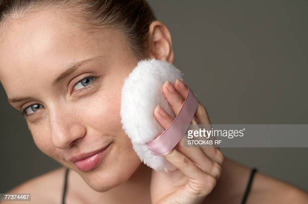Young woman removing makeup with a cotton pad, close-up