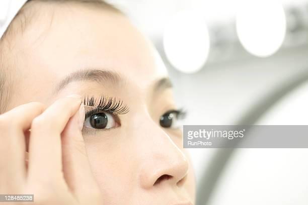 young woman removing the false eyelashes