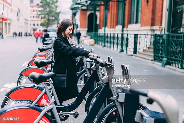 Young woman renting bicycle on street in London