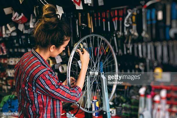 Young woman repairing a bike