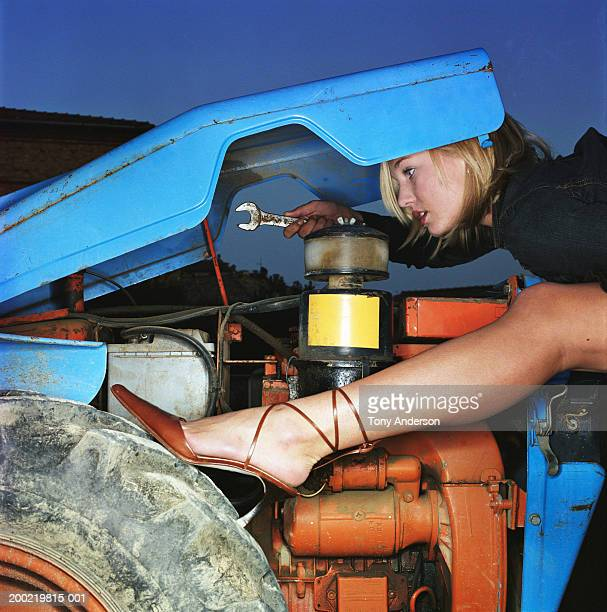 Young woman repairing engine on tractor, side view