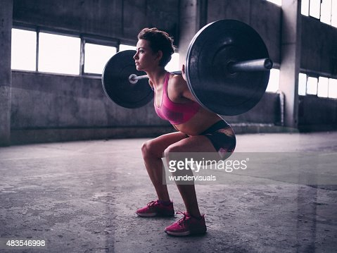 Young woman resting a heavy barbell on her shoulders