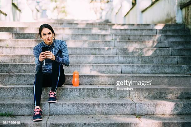Jeune femme au repos après un jogging dans le parc