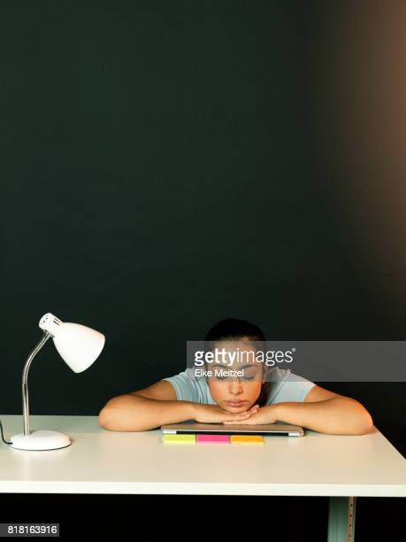 young woman resting at desk