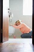 Teenage Girl Feeling Unwell In Bathroom Kneeling By Toilet