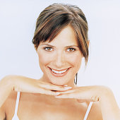 Young woman resting chin on hands, smiling, portrait