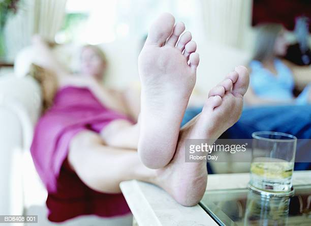 Young woman resting feet on coffee table (focus on feet)