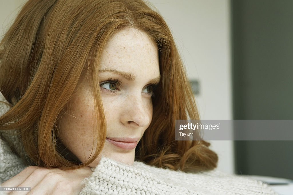 Young woman resting head on arms, looking away, close-up : Stock Photo