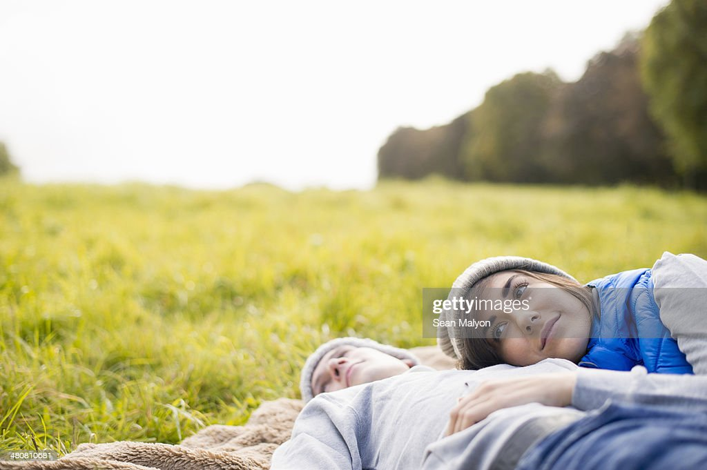 Young woman resting head on man's chest in park : Stock Photo