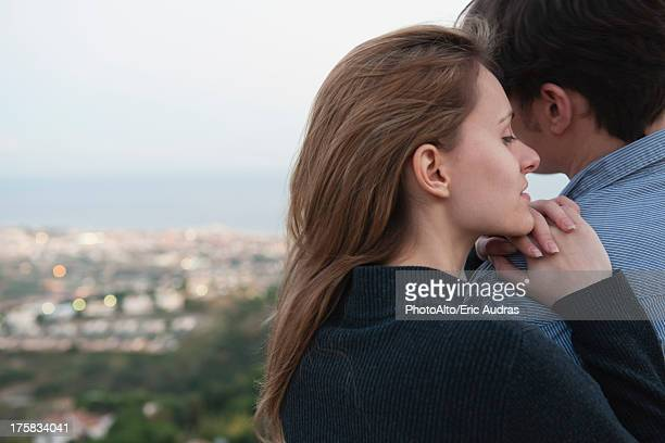 Young woman resting head on man's shoulder, rear view