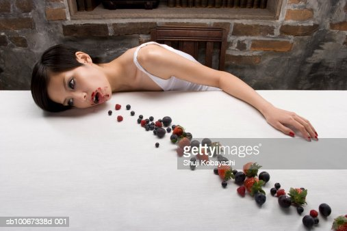 Young woman resting head on table with berries in line, elevated view : Stock Photo