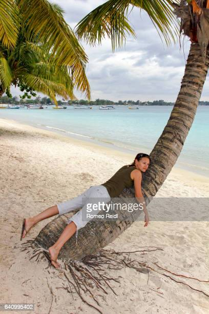 Young woman resting on a palm in a beach in Mauritius