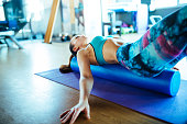 Young woman wearing a crop top resting on pilates foam roller