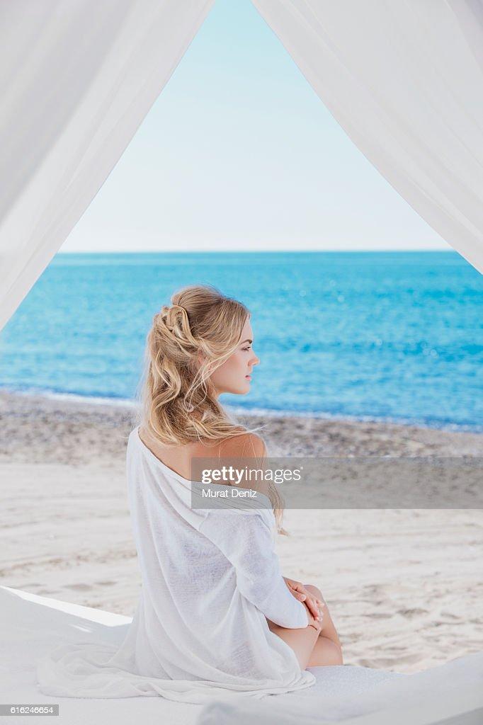 Joven mujer descansando en la playa : Foto de stock